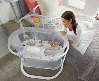 baby sleeping in Fisher-Price Soothing Motions Bassinet near the mom