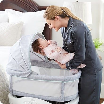 Mom Adding baby in Graco Move And Soothe Bassinet