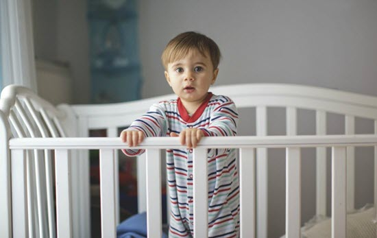 toddler standing in a big crib