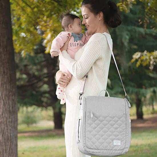 mom holding baby and SUNVENO Infant Travel bassinet